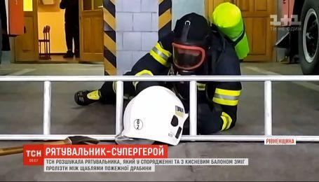 Пожарник из города Сарны в снаряжении может пролезть между ступенями пожарной лестницы