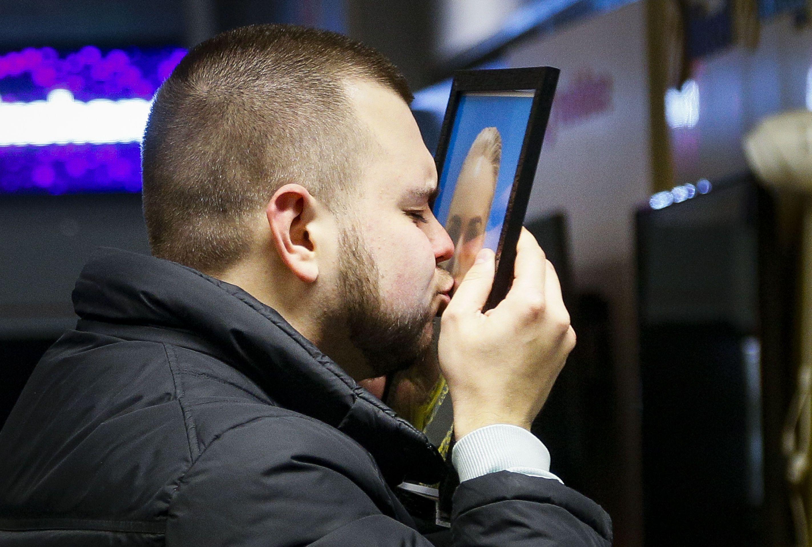 Чоловік цілує фото бортпровідниці Юлії Сологуб, авіакатастрофа МАУ під Тегераном