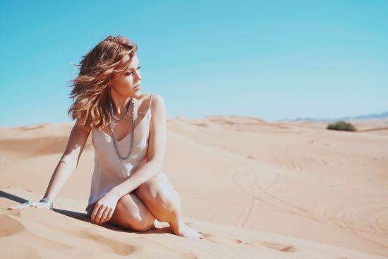 Тендітна Alyosha у легкій сукні засвітила оголені ніжки посеред пустелі