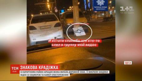 Крадіжка в прямому ефірі: в одеській Аркадії дівчина поцупила дорожній знак