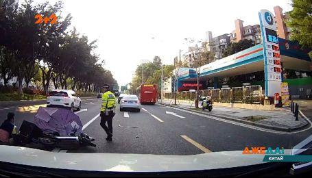 У Китаї водій електро-скутера тікав від копа та потрапив під колеса авто