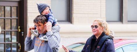 В розовых лосинах и куртке: Эми Шумер вышла на прогулку с мужем и сыном