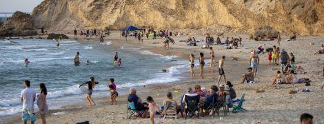 Кружки наполняются пивом, а на пляжи возвращаются люди: ослабление карантина разных стран в фото