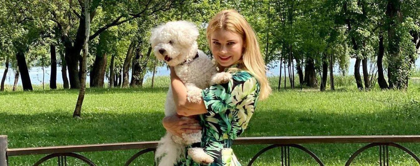 В платье с флористическим принтом и с собакой на руках: Лидия Таран прогулялась по парку