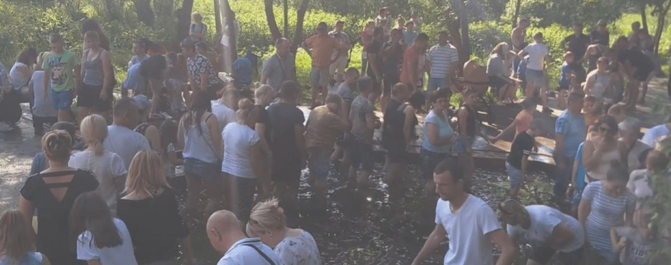 """Зцілялись від коронавірусу: близько сотні людей влаштували масове купання в """"чудодійному"""" джерелі біля Львова"""