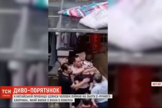 У Китаї чоловік на льоту піймав дворічного хлопчика, який випав з 5 поверху