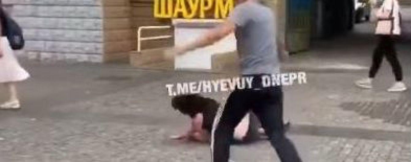 В Днепре мужчина посреди улицы ногами избил женщину, она потеряла сознание: появилось видео