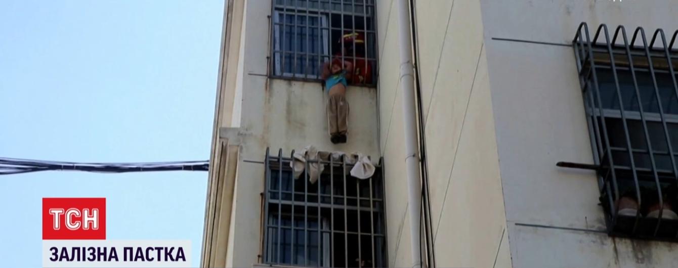 В Китае ребенок головой застрял в железной решетке на окне