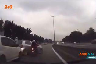 На трассе Малайзии из-за ошибки водителей скутерист вылетел прямо под колеса авто