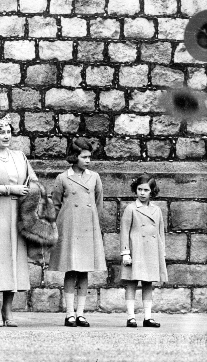 Будущие король и королева, Георг, герцог Йоркский и Елизавета, герцогиня Йоркская со своими дочерьми, принцессами Елизаветой и Маргарет в 1932 году смотрят парад бойскаутов в Виндзорском замке, Беркшир.