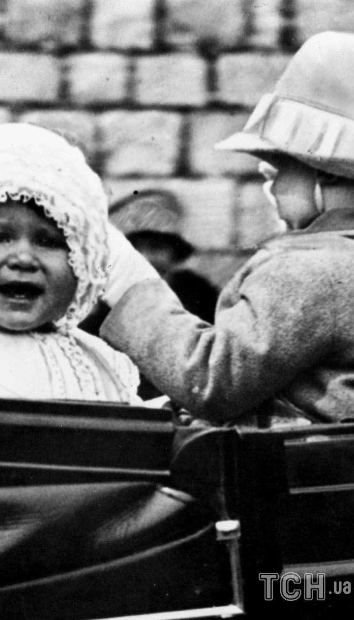 Маленькая принцесса Елизавета изображена в 1927 году. Фотография сделана, когда маленькая принцесса была взята на прогулку по территории Виндзорского замка.