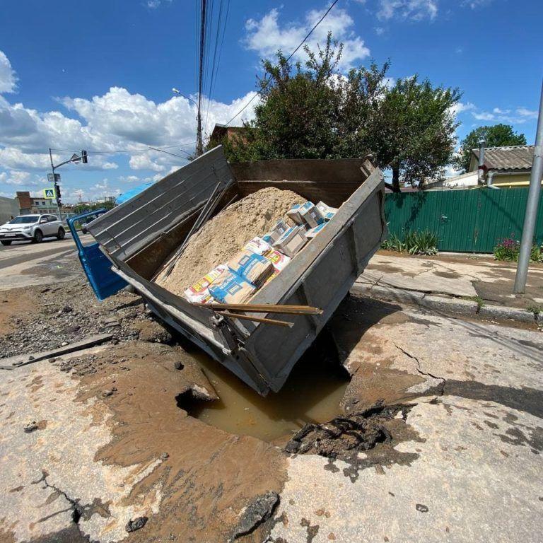 По коліна у воді, а колеса під асфальтом: на затопленій вулиці у Хмельницькому провалилася вантажівка