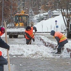 У Києві комунальники під снігом кинулись укладати асфальт