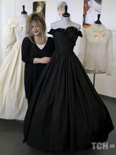 Дизайнер Элизабет Эмануэль стоит с двумя платьями и блузкой, которые она спроектировала для принцессы Дианы на аукционе в Лондоне. / © Associated Press