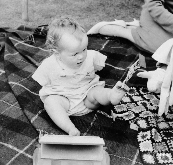 Маленький Томас Йенделл поднимает игрушки ногами. Лондон, 1 августа 1963 года / © Associated Press