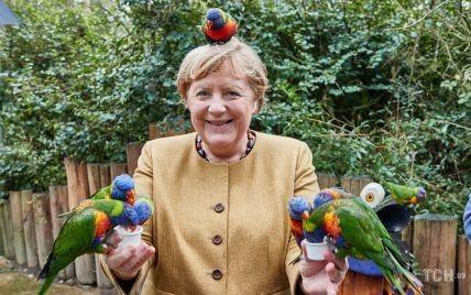 З папугою на голові: Ангела Меркель погодувала птахів у парку