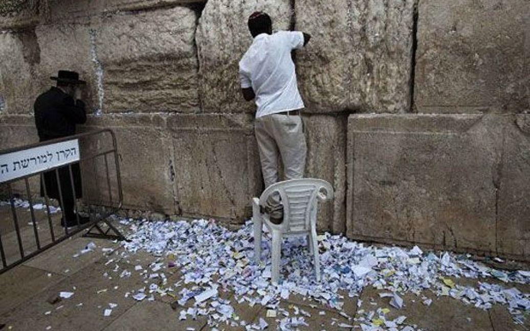 Єрусалим. Співробітник прибирає паперові записки і молитви, залишені в Стіні Плачу, під час підготовки до святкування єврейського Нового року. / © AFP