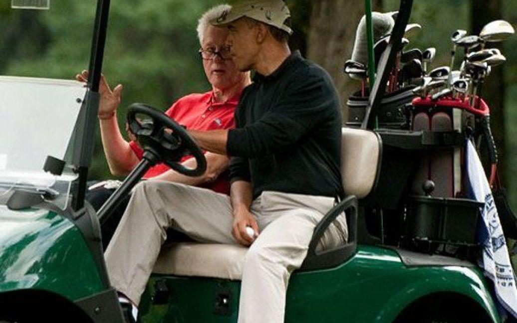 США, база Ендрюс. Президент США Барак Обама і екс-президент США Білл Клінтон розмовляють під час поїздки у гольф-карі після завершення гри на базі Ендрюс. / © AFP