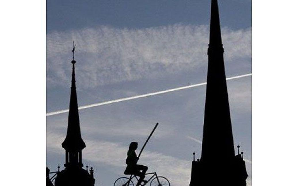 Німеччина, Галле. Жінка-канатоходець на велосипеді пересувається по мотузці над ринковою площею перед церквою у місті Галле, Східна Німеччина. / © AFP