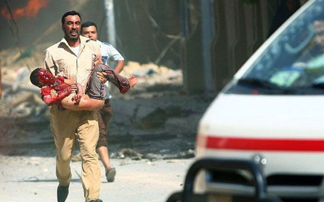 Ірак, Кербела. Чоловік несе на руках дитину, поранену під час вибуху в місті Кербела. В результаті вибуху у державному закладі, загинули щонайменше дев'ять осіб. / © AFP