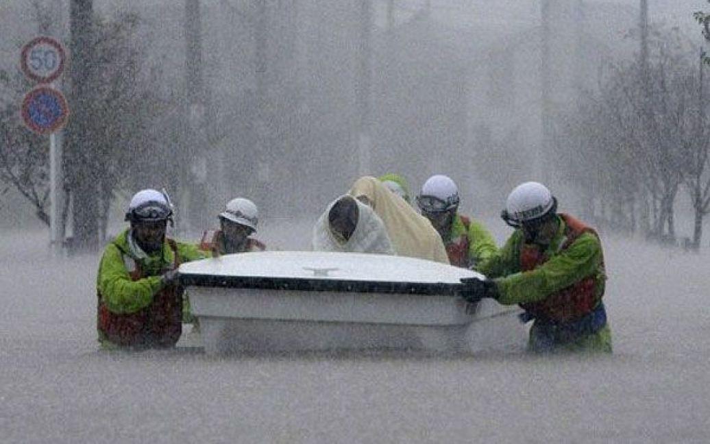Японія, Нагоя. Рятувальники перевозять евакуйованих у човні через затоплене місто Нагоя у префектурі Аїті. Сотні тисяч людей в Японії були змушені залишити свої домівки через наближення потужного тайфуну, який приніс із собою проливні дощі і загрозу зсувів і паводків. / © AFP