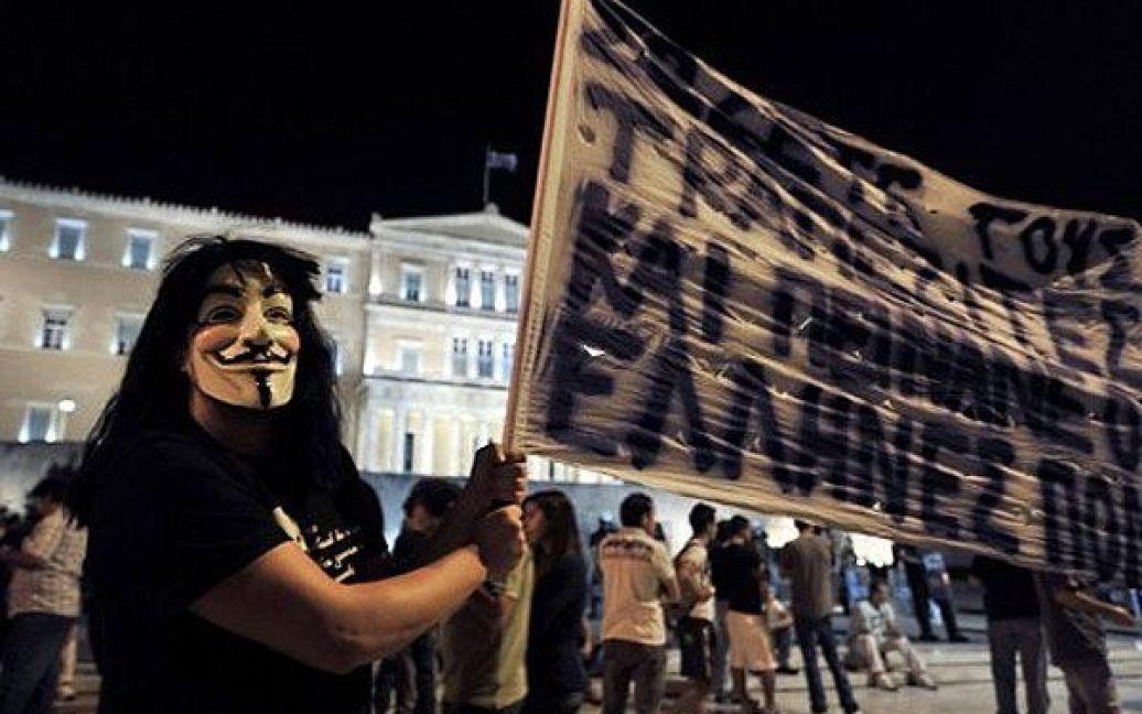 Греція, Афіни. Демонстрант у масці бере участь в акції протесту перед парламентом Греції проти нових заходів жорсткої економії. / © AFP