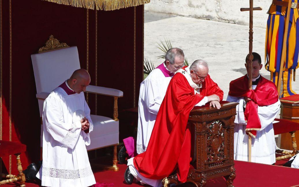 Папа Франциск стоит на коленях во время мессы в Ватикане / © Reuters