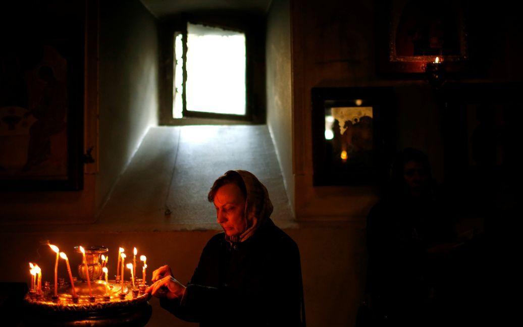 Женщина зажигает свечу в Тбилиси, Грузия / © Reuters