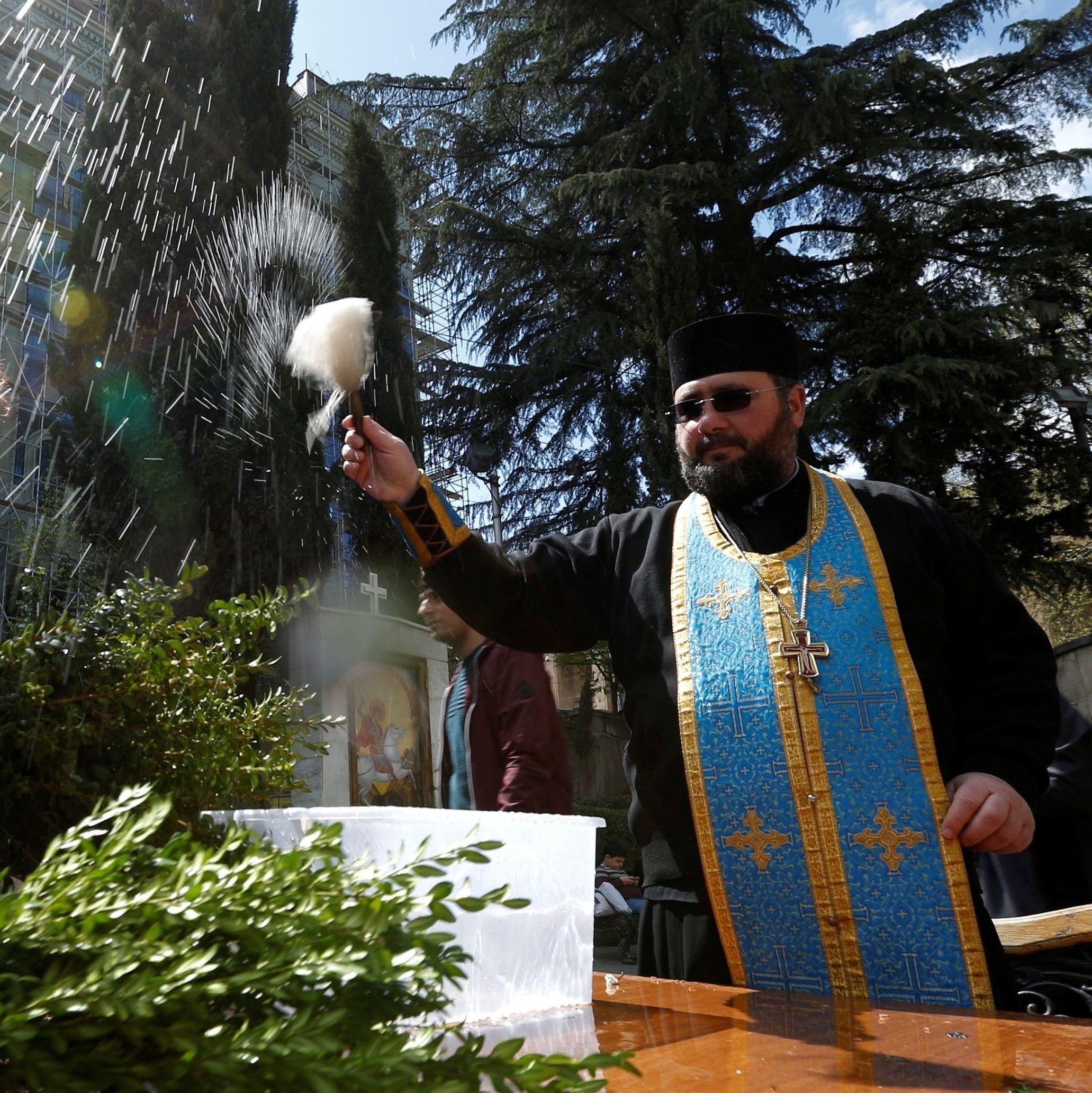 Священник благословляет верующих святой водой в Тбилиси, Грузия / © Reuters