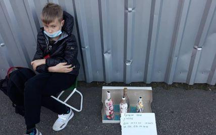 У Києві біля метро хлопчик продає оригінальні, декоровані власноруч пляшки: фото