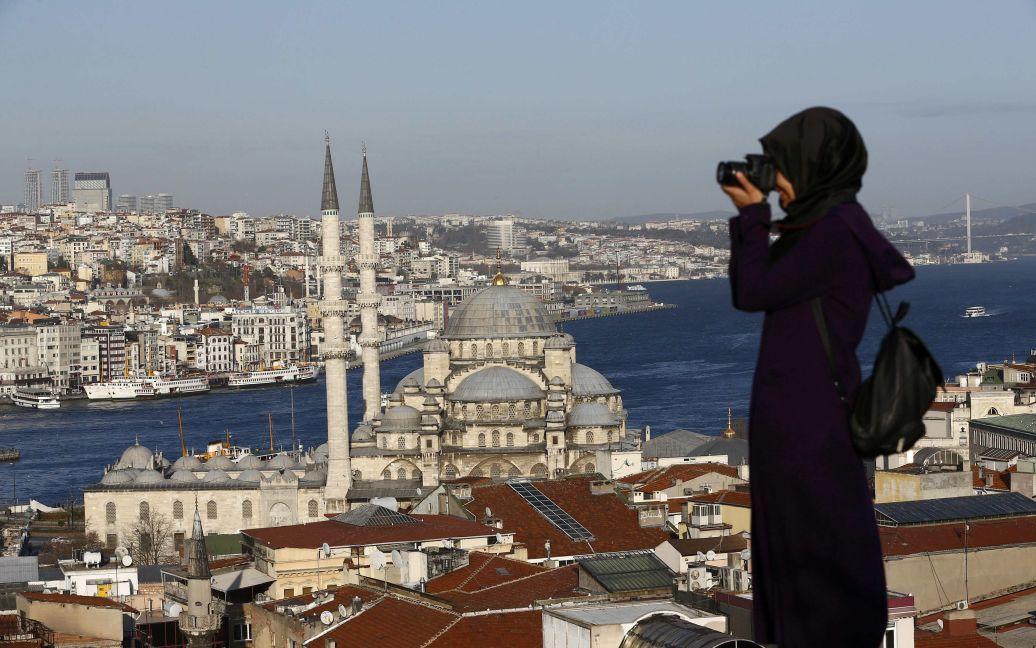 Жінка фотографує перед новою мечеттю поряд з протокою Босфор у Стамбулі, Туреччина. 12 січня сирійський терорист-смертник вчинив вибух в історичному центрі Стамбула неподалік від Блакитної мечеті, внаслідок якого загинули 10 людей. / © Reuters