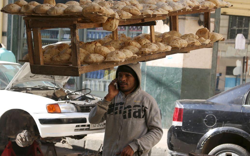 Працівник пекарні розмовляє по мобільному, несучи на голові піднос свіжоспеченого хліба з місцевої пекарні на вулиці в Каїрі, Єгипет. / © Reuters