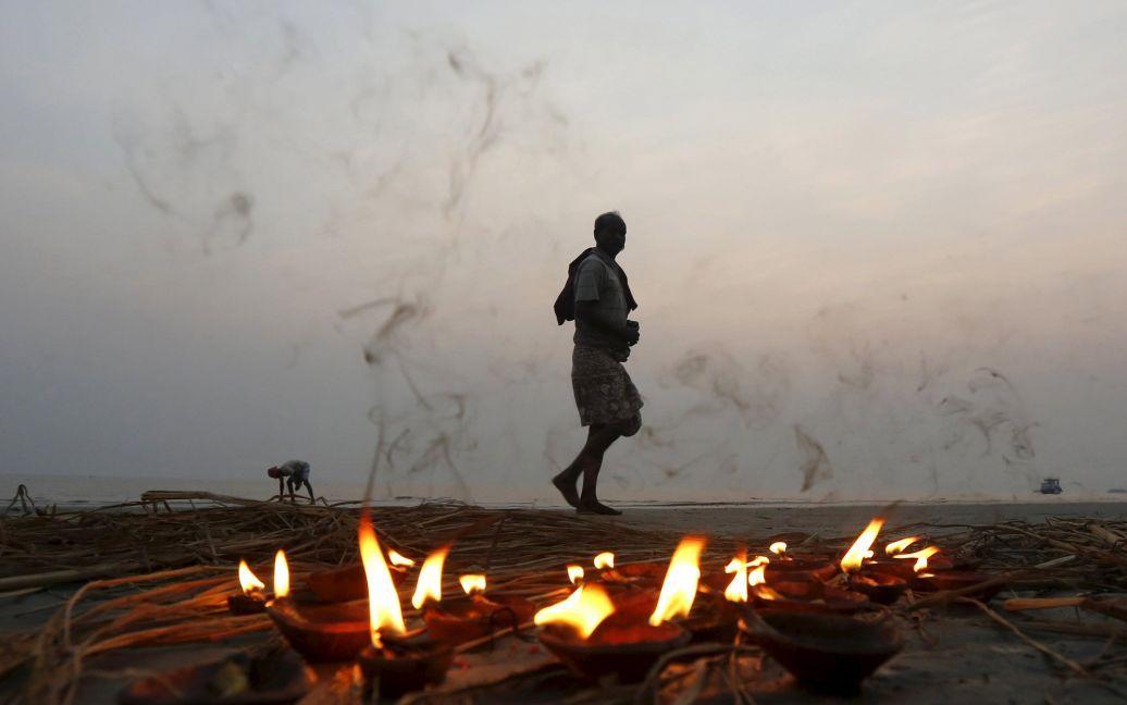 Індуський паломник проходить повз ряд освітлених ламп після прийняття священного обмивання в місці злиття річки Ганг і Бенгальської затоки на острові Сагар, на південь від Калькутта, Індія. / © Reuters