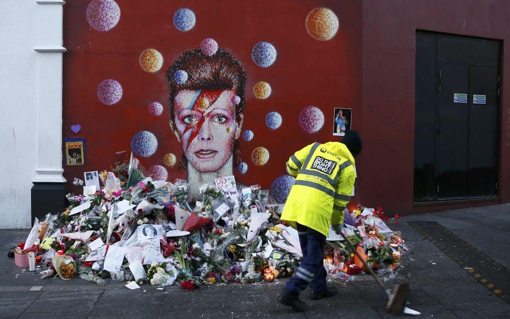 Працівник підмітає тротуар поруч з фрескою Девіда Боуї в Брікстоні, південному Лондоні, Великобританія. 69-річний співак помер від раку через два дні після випуску свого останнього альбому. / © Reuters