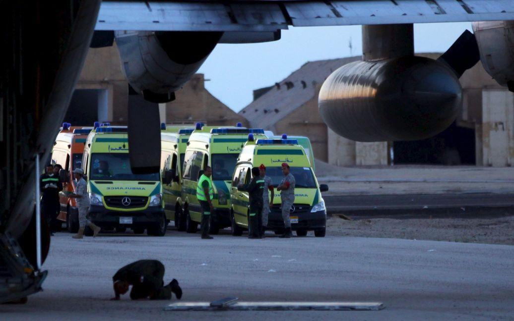 Мужчина молится на фоне спасателей, которые работают на месте падения самолета. / © Reuters